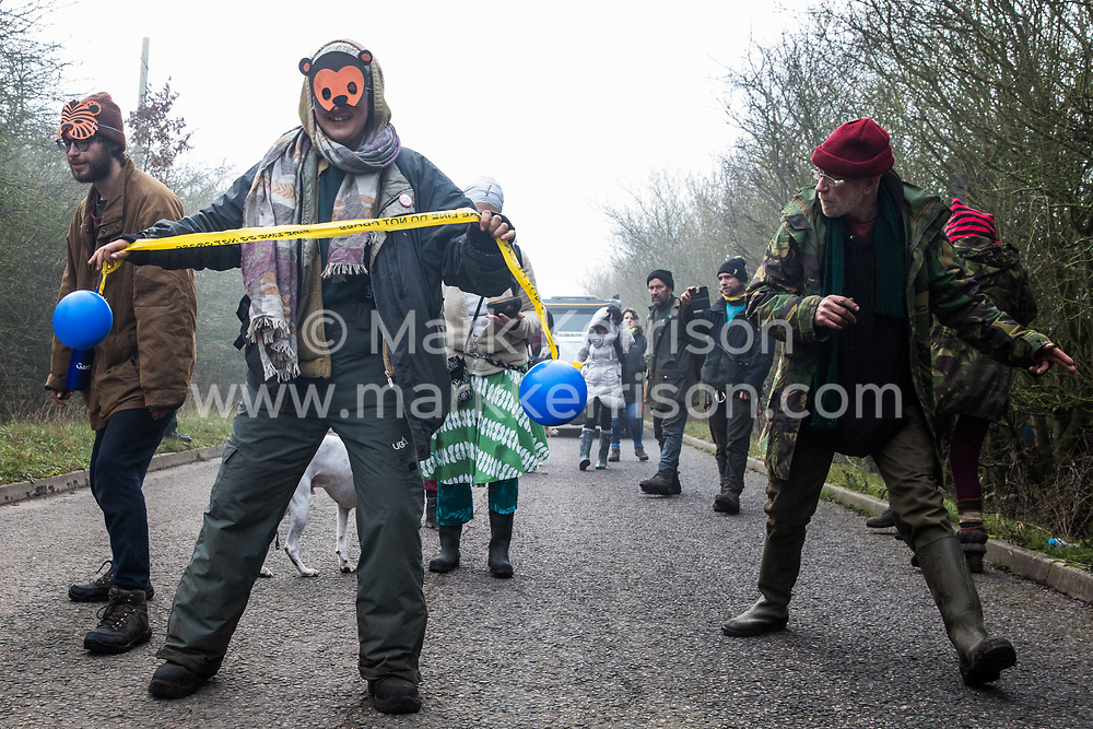 Denham, UK. 6th February, 2020. Environmental activists from Save the Colne Valley, Stop HS2 and Extinction Rebellion walk at a snail's pace along a road in order to block a security vehicle and truck delivering fencing and other supplies to be used for works associated with the HS2 high-speed rail link close to the river Colne at Denham Ford. Works planned in the immediate vicinity include the felling of trees and the construction of a Bailey bridge, compounds and fencing, some of which in a wetland nature reserve adjacent to a Site of Metropolitan Importance for Nature Conservation (SMI).