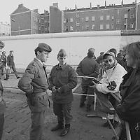 Eine Journalistin aus der Bundesrepublik sucht das informelle Gespräch mit Grenzsoldaten. In ihren Gesichtern dominiert die Skepsis. Im Hintergrund DDR-Bürger in schier endloser Zahl auf ihrem Weg nach Westberlin.