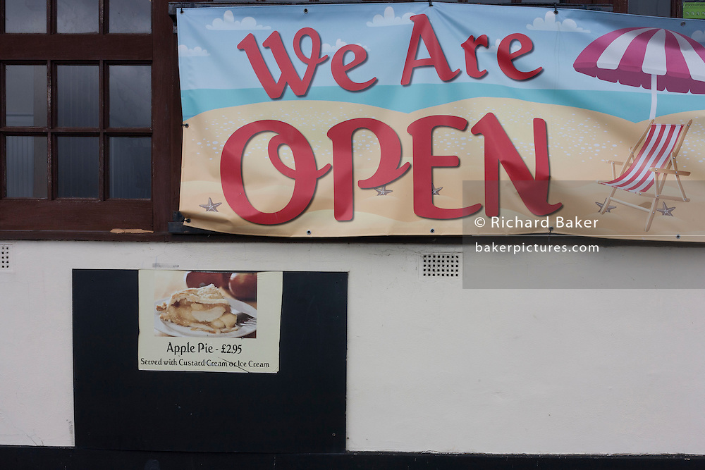 A banner telling customers a seedy cafe is still open, on the Western Esplanade at Southend.