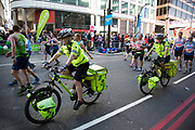 London, UK. Sunday 13th April 2014. Competitors running in the main public event of the Virgin Money London Marathon 2014. These runners take part and raise huge sums fo money for charity organisations. Paramedics on bicycles look after people at the event.