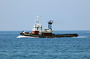 A tug boat steaming to help a ship aproach the dock, Milazzo, Sicily, July 2006