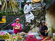 04 AUGUST 2017 - PAYANGAN, BALI, INDONESIA: Women make offering baskets to sell to people who go to the Hindu temple in the local market in Payangan, about 45 minutes from Ubud. Most markets in Hindu majority Bali have their own temple. Bali's local markets are open on an every three day rotating schedule because venders travel from town to town. Before modern refrigeration and convenience stores became common place on Bali, markets were thriving community gatherings. Fewer people shop at markets now as more and more consumers go to convenience stores and more families have refrigerators.      PHOTO BY JACK KURTZ