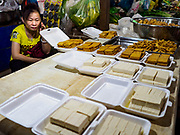"""14 FEBRUARY 2019 - SIHANOUKVILLE, CAMBODIA: A Chinese woman sells tofu in the Leu Market in Sihanoukville. There are thousands of Chinese workers in Sihanoukville who work to support the casino and hotel industry in the town. There are about 80 Chinese casinos and resort hotels open in Sihanoukville and dozens more under construction. The casinos are changing the city, once a sleepy port on Southeast Asia's """"backpacker trail"""" into a booming city. The change is coming with a cost though. Many Cambodian residents of Sihanoukville  have lost their homes to make way for the casinos and the jobs are going to Chinese workers, brought in to build casinos and work in the casinos.      PHOTO BY JACK KURTZ"""