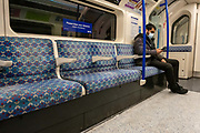 A man wearing a mask sits alone and checks his phone in a train carriage on the Victoria Line of the London Underground during rush hour in London on the 26th of January 2021. London, United Kingdom. All passengers on public transport are expected to wear a mask and signs for social distancing are everywhere.