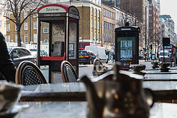 A modern public telephones carrying illuminated advertising is just yards from an older, still working version, adding to the clutter of signs, lampposts, sandwich boards, bus shelters and street furniture on Edgeware Road in London. LONDON, February 12 2019.