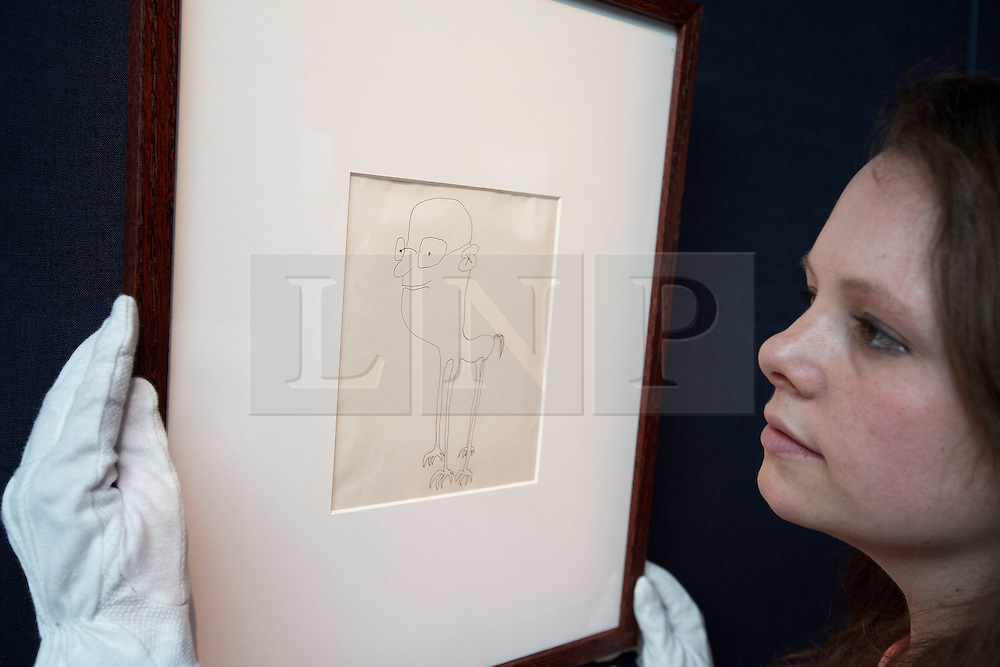 """© Licensed to London News Pictures. 21/03/2014. London, UK. A member of Sotheby's auction house staff adjusts 'untitled illustration of a bespectacled creature with clawed feet' (GB£3,600-4,800) a drawing by the late Beetles singer John Lennon, allegedly the piece that brought him to the attention of his future wife Yoko Ono, during the press view for a new sale at Sotheby's auction house in London today (21/03/2014). The auction, entitled """"You Might Well Arsk"""", features original drawings and manuscripts by the singer from 1964-1965. Photo credit: Matt Cetti-Roberts/LNP"""