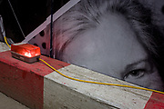 A woman's eye a construction site hoarding peers over the top of a timber traffic barrier and wiring, on the corner of Limeburner Lane and Ludgate Hill, EC4. Yellow wiring and an illuminated red light alerts others to the industrial hazard. The construction and development company Skanska is responsible for its design, maintaining a clean and tidy site, separating the dangers of the site and Londoners at street level.