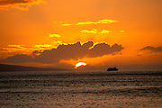 Setting sun behind clouds over the island of Lanai and the Lahaina-Lanai ferry, West Maui, Hawaii