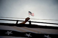 A representative from the non-profit community organization Village Laguna, waves a flag from atop a double-decker bus during the 45th Annual Laguna Beach Patriots Day Parade Saturday March 5, 2011.