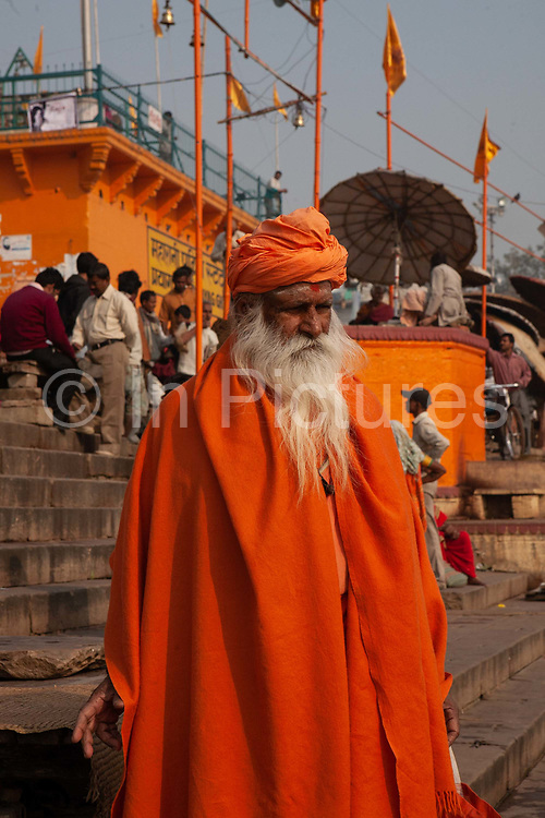 A Sadhu / Babba in orange robes on the banks of the Ganges on 21st December 2009 in Varanasi / Benares, Uttar Pradesh, India. According to Hindu mythology, Varanasi was founded by Shiva, one of three principal deities along with Brahma and Vishnu, and is seen as a significant and holy place to followers of the Hundu faith.