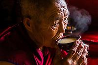 A Buddhist nun drinking yak butter tea, Drepung Monastery, Tibet (Xizang), China
