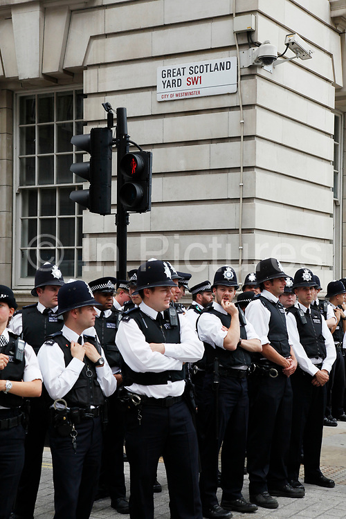 Police gather to block off Great Scotland Yard. This was a small street running east from the northern end of Whitehall, parallel with Whitehall Place. The original Metropolitan Police Commissioner's office (No. 4 Whitehall Place) backed on to it, and A Division was based there in the back of the building. The name became colloquially attached to the headquarters of the Metropolitan Police, especially as additional buildings were acquired to house branches of the expanding force.