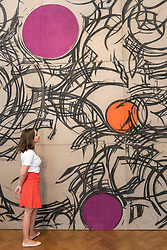 """© Licensed to London News Pictures. 25/06/2018. LONDON, UK. A staff member views an artwork by Wanda Czelkowska. Preview of """"Lands of Lads, Land of Lashes"""", an exhibition of sculptures and paintings by three female artists of the1960s and 1970s - Rosemarie Castoro, Wanda Czelkowska and Lydia Okumura - specialising in Minimal and Post-Minimal art.  The exhibition, held at Galerie Thaddaeus Ropac in Mayfair, runs 25 June to 11 August 2018.  Photo credit: Stephen Chung/LNP"""