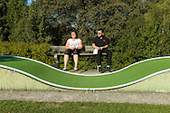 Father and daughter take a break while playing midget golf at a resort in Belgium