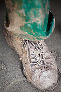 Hiker Liana Welty's leather boot and rain pants covered in wet mud on Third Beach, Olympic National Park, Washington.