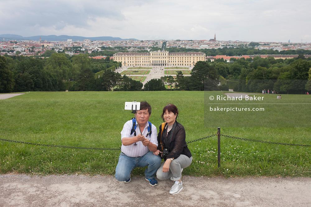 Foreign tourists take a selfie with a background of Schloss Schonbrunn, in Vienna, Austria, EU.