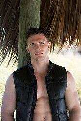 sexy All American man in a vest under a beach hut