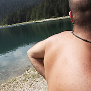 """a man near a Dorumitor lake. There are several arguments about the derivation of the name  """"Montenegro"""", one of these relates to dark and deep forests  that once covered the Dinaric Alps, as it was possible to see them from the sea. <br /> Mostly mountainous with 672180 habitants on an area of 13812 Km², with a population density of  48 habitants/Km². <br /> It borders with Bosnia, Serbia, Croatia, Kosovo and Albania but  Montenegro has always been alien to the bloody political events that characterized Eastern Europe in recent decades. <br /> From 3 June 2006, breaking away from Serbia, Montenegro became an independent state. <br /> In the balance between economy devoted to sheep farming and a shy tourist, mostly coming from Bosnia and Herzegovina, Montenegro looks to Europe with a largely unspoiled natural beauty. <br /> Several cities in Montenegro, as well as the park Durmitor, considered World Heritage by UNESCO but not yet officially because Montenegro has yet to ratify the World Heritage Convention of UNESCO."""