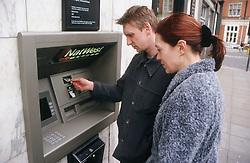 Couple standing in street using cash machine,