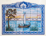 Traditional Portuguese painted tiles (Azulejos) depicting a sail boat harvesting seaweed in the Aveiro Lagoon, Portugal