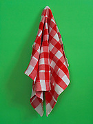 kitchen towel hanging against a green wall
