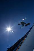 Female snowboarder flying over the vert.