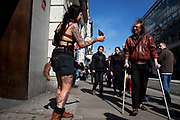 Woman giving out flyers for a tattoo shop to shoppers in central London on Oxford Street. UK. Listening to music she was dancing whilst happily giving out information and chatting to potential customers.