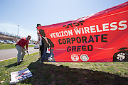 Pete Sanders and Jim Frazier of CWA Local 13000 put up a banner while picketing outside a Verizon Wireless store near Bloomsburg, Pennsylvania.