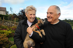 A retired couple enjoy their leisure time with their dog in the garden, Cumbria.  Model Released.