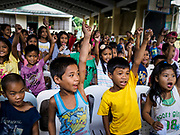 28 JANUARY 2018 - LEGAZPI, ALBAY, PHILIPPINES: Children participate in an activity organized by Jollibee, a Filipino fast food outlet, at the evacuation shelter for people from Barangay (community) Matanag in Albay Central School in Legazpi. People from the community have been in the shelter since Mayon volcano started erupting two weeks ago. There are about 500 families at the shelter, around 2,000 people. More than 80,000 people have been evacuated from communities around the volcano and are living in shelters and camps outside of the evacuation zone. The Philippine government is preparing to house the people for up to three months.      PHOTO BY JACK KURTZ