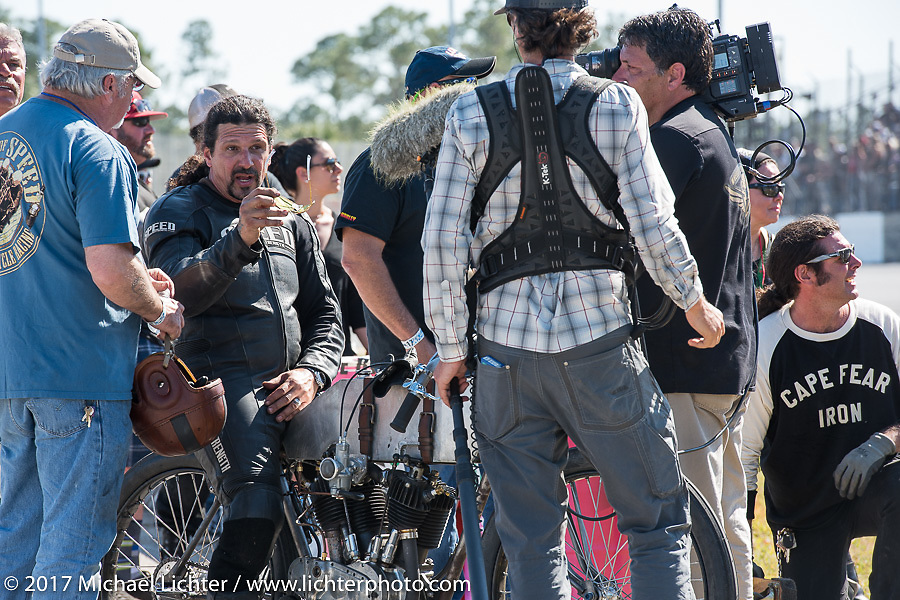 Billy Lane on his 1924 single-speed 1924 Harley-Davidson Model J 62 cubic inch racer gets interviewed at the end of Billy's Son's of Speed race during Daytona Bike Week. New Smyrna Beach, FL. USA. Saturday March 18, 2017. Photography ©2017 Michael Lichter.