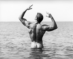 rear view of a nude bodybuilder in the ocean