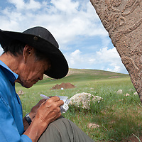 """Mongolian archaeologist Tovuudorj Sanjmyatov (""""Sasha"""") (MR) sketches carvings on a 2700+ year-old, bronze age deer stone monument at Ulaan Tolgai archaeological site near Lake Erkhel, north of Muren, Mongolia.  Sasha is a pioneer Mongolian researcher, who did much work and publication during the Soviet era.   <br /> MS0702_060626_0135.NEF"""