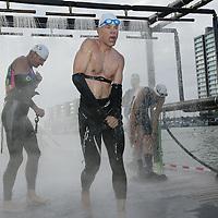 Nederland.Almere Haven.27 augustus 2005.<br /> Na het 1e onderdeel van de Holland Triathlon, de 4 km afstandzwemmen in het IJsselmeer rennen de deelnemende atleten uit het water door de douche naar het volgende onderdeel het wielerrennen.<br /> op de foto staat een deelnemer onder de buitendouche snel zijn wetsuit  uit te trekken alvorens verder te rennen.<br /> Participants in the Holland Triathlon 2005.