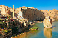 Remains of medieval Artukid Old Tigris Bridge – Built in 1116 by Artukid Fahrettin Karaaslan, the biggest in Anatolia at the time, with the old town Hasankeyf and its ruins on the cliffs abover the river Tigris. The minaret is of the El Rizk Mosque built 1409.  Turkey. 1 .<br /> <br /> If you prefer to buy from our ALAMY PHOTO LIBRARY  Collection visit : https://www.alamy.com/portfolio/paul-williams-funkystock/hasankeyf-turkey.html<br /> <br /> Visit our PHOTO COLLECTIONS OF TURKEY HISTOIC PLACES for more photos to download or buy as wall art prints https://funkystock.photoshelter.com/gallery-collection/Pictures-of-Turkey-Turkey-Photos-Images-Fotos/C0000U.hJWkZxAbg
