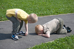 Boy looking after his brother after a fall,