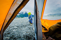 A warmly dressed two year old boy explores outside a tent on a rocky beach next to Bear Lake, Kenai Fjords National Park, Alaska.