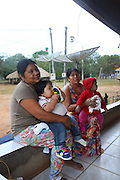 Surui, families, on the verandah with hammock, in their home<br /><br />An Amazonian tribal chief Almir Narayamogo, leader of 1350 Surui Indians in Rondônia, near Cacaol, Brazil, with a $100,000 bounty on his head, is fighting for the survival of his people and their forest, and using the world's modern hi-tech tools; computers, smartphones, Google Earth and digital forestry surveillance. So far their fight has been very effective, leading to a most promising and novel result. In 2013, Almir Narayamogo, led his people to be the first and unique indigenous tribe in the world to manage their own REDD+ carbon project and sell carbon credits to the industrial world. By marketing the CO2 capacity of 250 000 hectares of their virgin forest, the forty year old Surui, has ensured the preservation, as well as a future of his community. <br /><br />In 2009, the four clans and 25 Surui villages voted in favour of a total moratorium on logging and the carbon credits project. <br /><br />They still face deforestation problems, such as illegal logging, and gold mining which causes pollution of their river systems