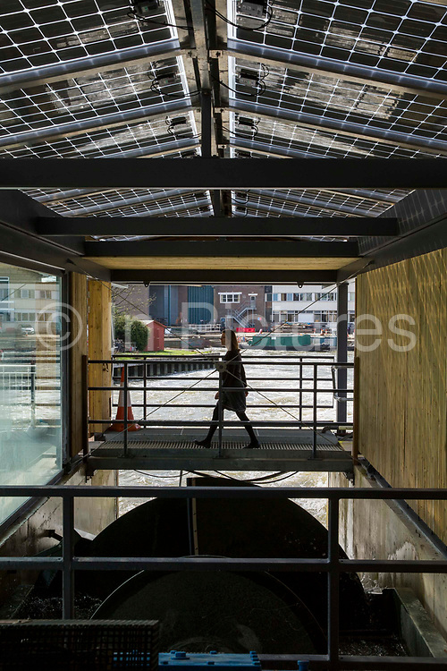 A women walks over a bridge above the Archimedean screw hydropower system of the Osney Lock Hydro on the River Thames in Oxford, England, United Kingdom.  It is the first community owned hydropower scheme to be built on the River Thames, set up by local residents in 2002, it generates clean, green electricity and a source of income.  The building has solar photovoltaic array panels to maximise green energy production.
