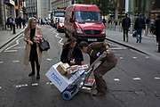 While crossing the road with a Royal Mail Parcelforce van in the road of the capital's financial district, a UPS courier is helped by a lady to pick up dropped parcels, on 5th October, 2017, in the City of London, England.