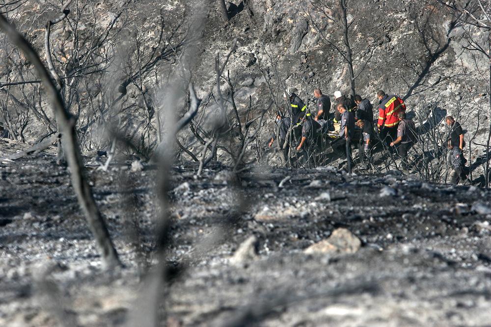 גופת הכבאי מעפולה  שנעדר נמצאה בוואדי סמוך למקום בו נשרף האוטובוס<br /> בתמונה הוא מפונה עי חבריו <br /> צילום עומר מסינגר<br /> 3.12.2010