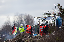 Licensed to London News Pictures. 03/03/2016. Calais, France. Contractors remove the Kurdish flag from a restaurant which is to be demolished. French authorities are clearing the southern half of the Calais 'Jungle' camp, which charities estimate to contain 3,500 people. Photo credit : Rob Pinney/LNP