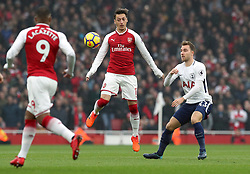 Arsenal's Mesut Ozil and Tottenham Hotspur's Christian Eriksen (right) battle for the ball during the Premier League match at the Emirates Stadium, London.