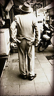 Rear view of smartly dressed man standing alone on the sidewalk with his hands in his pockets, Hanoi, Vietnam, Southeast Asia