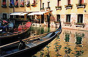 Gondolas sit in a waterway in Venice, Italy