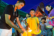 """17 NOVEMBER 2013 - BANGKOK, THAILAND: People light the candles on their krathongs before floating them in the Chao Phraya River near Wat Yannawa in Bangkok. Loy Krathong (also written as Loi Krathong) is celebrated annually throughout Thailand and certain parts of Laos and Burma (in Shan State). The name could be translated """"Floating Crown"""" or """"Floating Decoration"""" and comes from the tradition of making buoyant decorations which are then floated on a river. Loi Krathong takes place on the evening of the full moon of the 12th month in the traditional and they do this all evening on the 12th month Thai lunar calendar. In the western calendar this usually falls in November. The candle venerates the Buddha with light, while the krathong's floating symbolizes letting go of all one's hatred, anger, and defilements       PHOTO BY JACK KURTZ"""