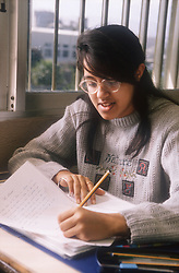 Secondary school girl sitting at desk in classroom writing notes,