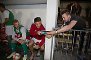 A fan asks the Karpatalya players for autographs at the 4 -2 victory for Karpatalya red against Szekely Land blue during the Conifa Paddy Power World Football Cup semi finals on the 7th June 2018 at Carshalton Athletic Football Club in the United Kingdom. The CONIFA World Football Cup is an international football tournament organised by CONIFA, an umbrella association for states, minorities, stateless peoples and regions unaffiliated with FIFA.