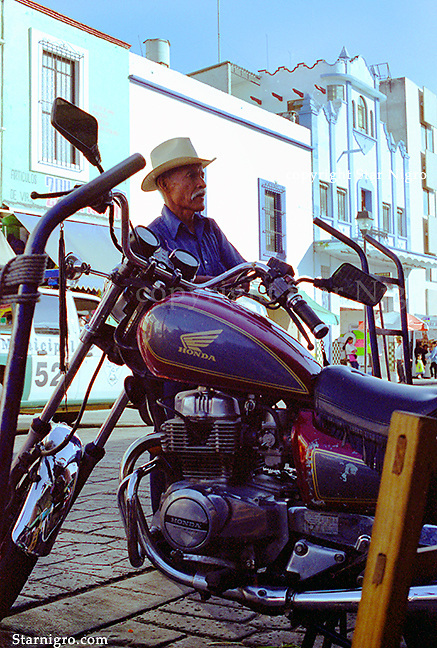 Motorcyclist of Mexico street scene photographed by Star Nigro.<br /> <br /> <br /> © 2021  All artwork is the property of STAR NIGRO.  Reproduction is strictly prohibited.