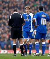 Photo: Daniel Hambury.<br />Arsenal v Cardiff City. The FA Cup. 07/01/2006.<br />Cardiff's Glenn Loovens (C) is about to be booked by referee Martin Atkinson.
